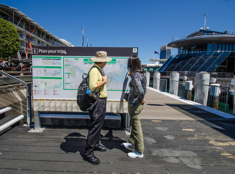 Tourists check out the map of Sydney at Darling Harbour. SYDNEY, AUSTRALIA NOVEMBER 2, 2016 Tourists check out the map at the promenade at Darling Harbour, one stock image