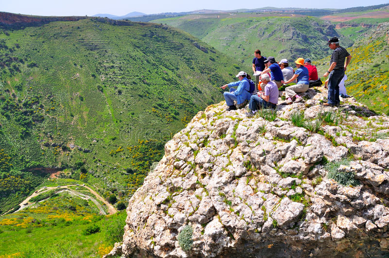 Tourists on cliff edge, Israel. A group of tourists resting on a cliff edge above a deep ravine in the galil, Israel stock photography