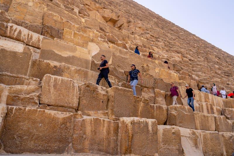 Tourists climbing the biggest Pyramid of Giza stock image