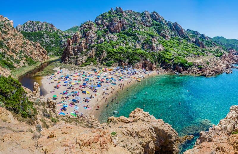 Tourists colorful sun umbrellas at Costa Paradiso Beach, Sardinia, Italy stock photo