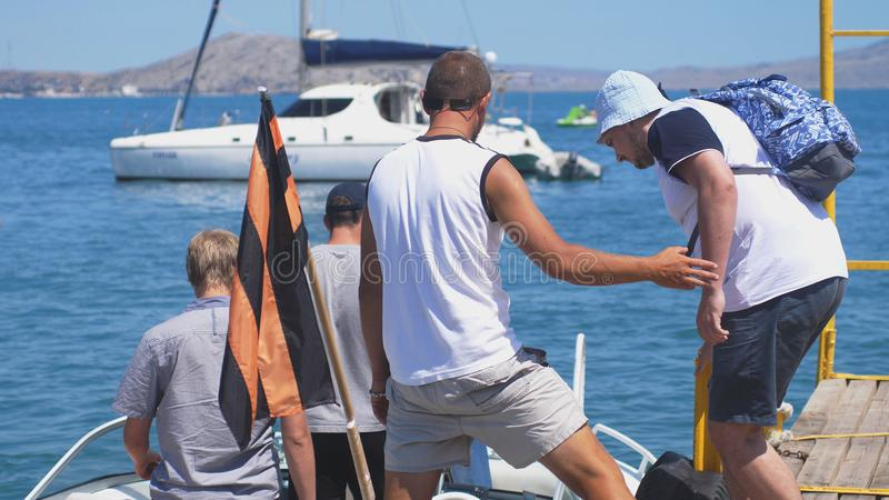 Russia, Crimea, 6 july 2017. Tourists are coming into the boat for a trip on an excursion at sunny summer day. Tourists are coming into the boat for a trip on stock photo