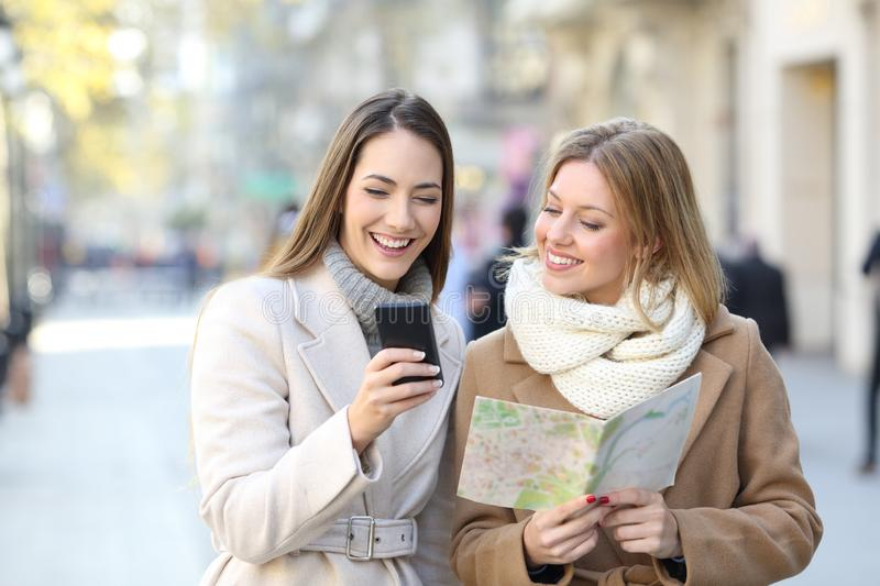 Tourists comparing phone and map in winter holiday stock photography