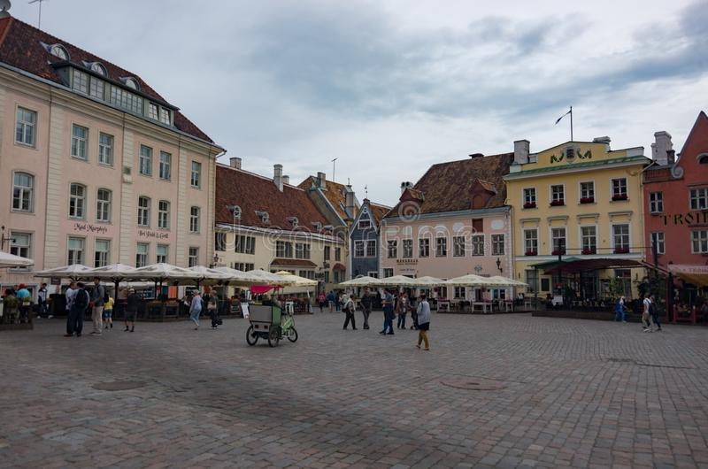 Tourists crowd the sidewalk cafes and shops in the medieval Tallinn Town Square in the walled city of Tallinn Estonia stock photography