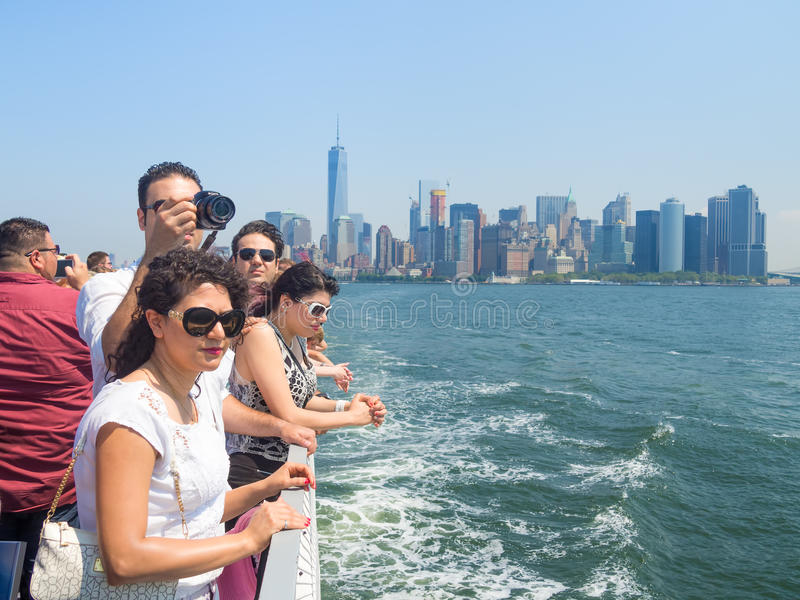 Tourists in a cruise ship on the bay of New York. NEW YORK,USA - AUGUST 16,2015 : Tourists in a cruise ship on the bay of New York with the Manhattan skyline on stock photo