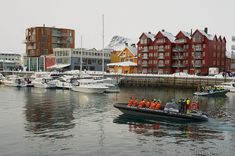 Tourists depart for boat safari from the harbor of Svolvaer, Norway. SVOLVAER, NORWAY - MARCH 26, 2011: Unidentified tourists depart for boat safari from the stock photography