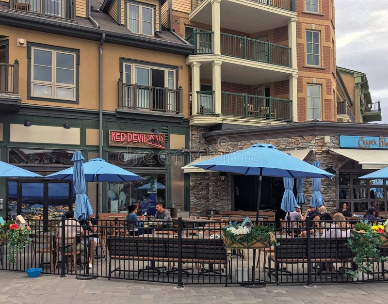 Tourists dining in Blue Mountain Village Canadian popular resort in summer royalty free stock photo
