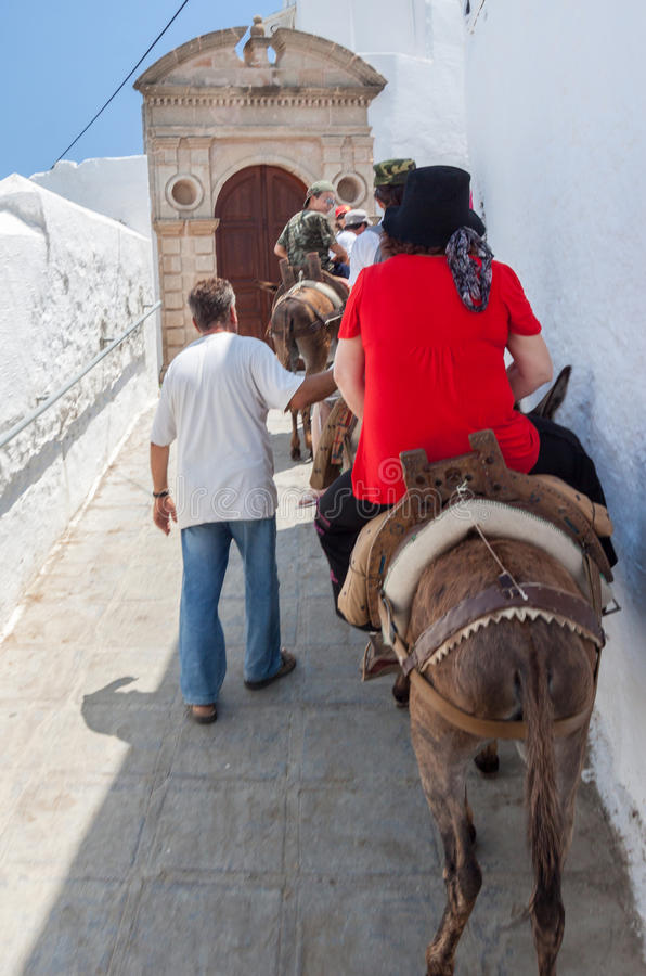 Tourists Donkeys Lindos Rhodes Greece. Tourists riding donkeys in Lindos, Rhodes Island, Greece stock images