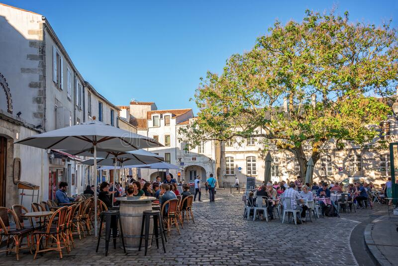 Tourists eating outdoor at restaurants terraces in summer in a picturesque square of the old town of La Rochelle France stock photography