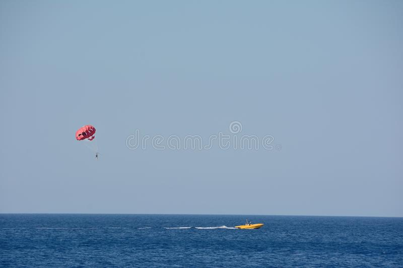 Tourists are engaged in parasailing in the distance against the blue sky and the sea.  royalty free stock photos