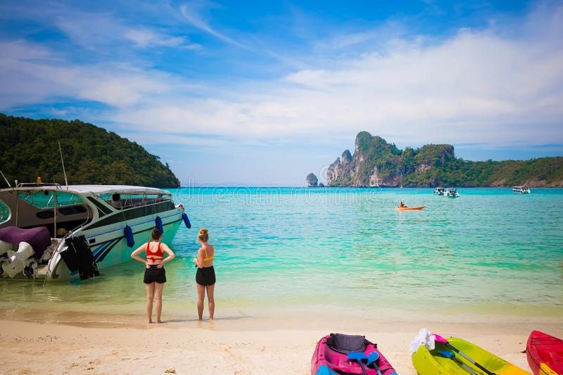 Tourists enjoy view on the Phi Phi island stayed on a sandy beach. Sunny day at the tropical island. Motor speed boat at the left. Kayaks on the sand and in royalty free stock photography
