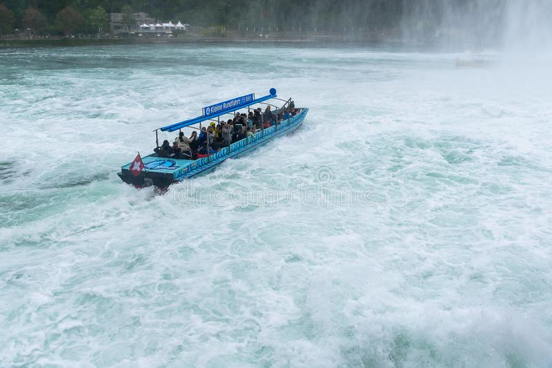 Tourists enjoying boat trip in Rheinfall waterfall in Switzerland royalty free stock photography