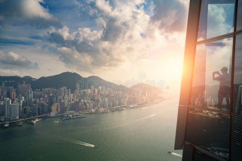 Tourists enjoying Hong Kong city views from the Sky 100 Observation Deck in West Kowloon at Hong Kong. Asian tourism, modern city royalty free stock image