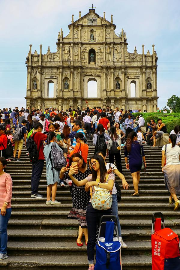 Ruins of st. paul`s, monte fort, macau with tourists. Tourists enjoying themselves taking selfies and sightseeing in front of the ruins of st. paul`s, monte fort royalty free stock photos