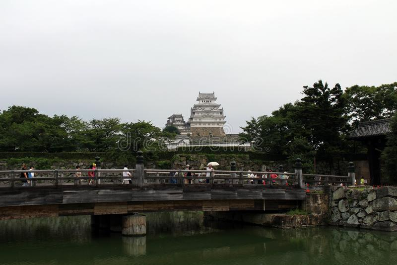 Tourists flocking to enter Himeji Castle, some are waiting on th. E bridge on a cloudy day. Pic was taken in Japan, August 2017 royalty free stock image