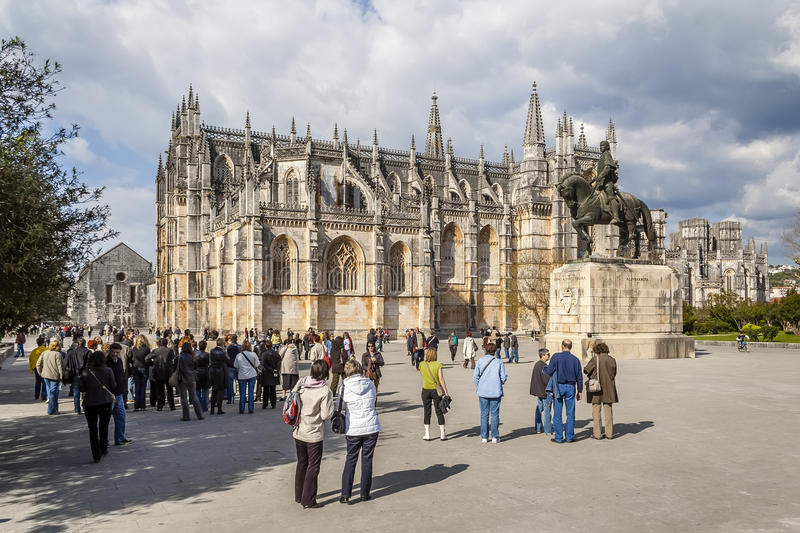 Tourists gathering around for a guided tour of the monastery. Batalha, Portugal - April 05, 2015: Tourists gathering around for a guided tour of the monastery stock photo