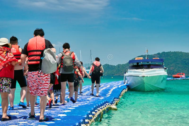 Tourists go by the boat at the pier plastic. Travelers in life jackets sit on board a sea speedboat. Concept activities at the sea stock photography