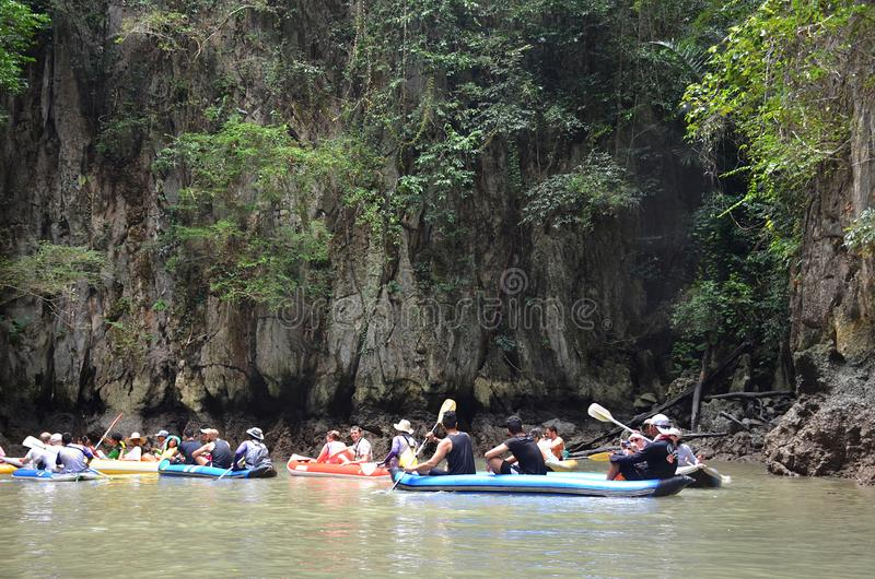 Tourists with guides swim in inflatable canoes among the giant cliffs. Tourists kayaking in Ao Phang Nga national park, Thailand royalty free stock photos