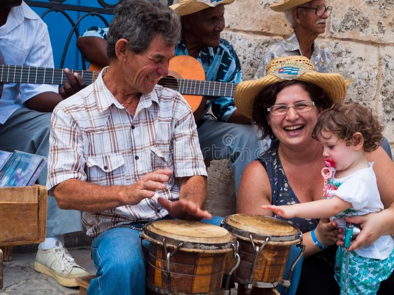 Tourists at Havana, mom and little daughter play with street musicians, Cuba stock image