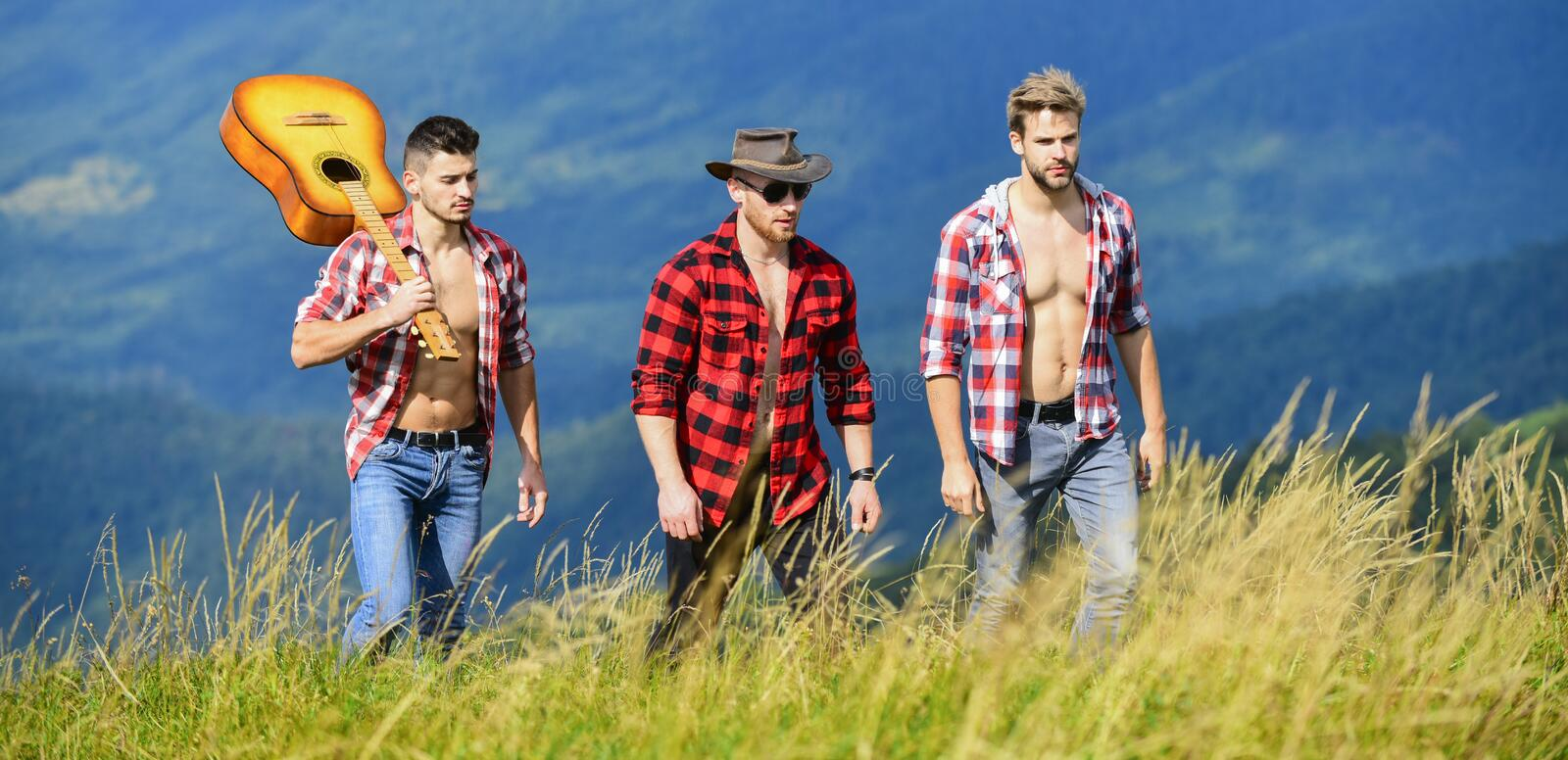 Tourists hiking concept. Hiking with friends. Enjoying freedom together. Long route. Group of young people in checkered. Shirts walking together on top of stock images