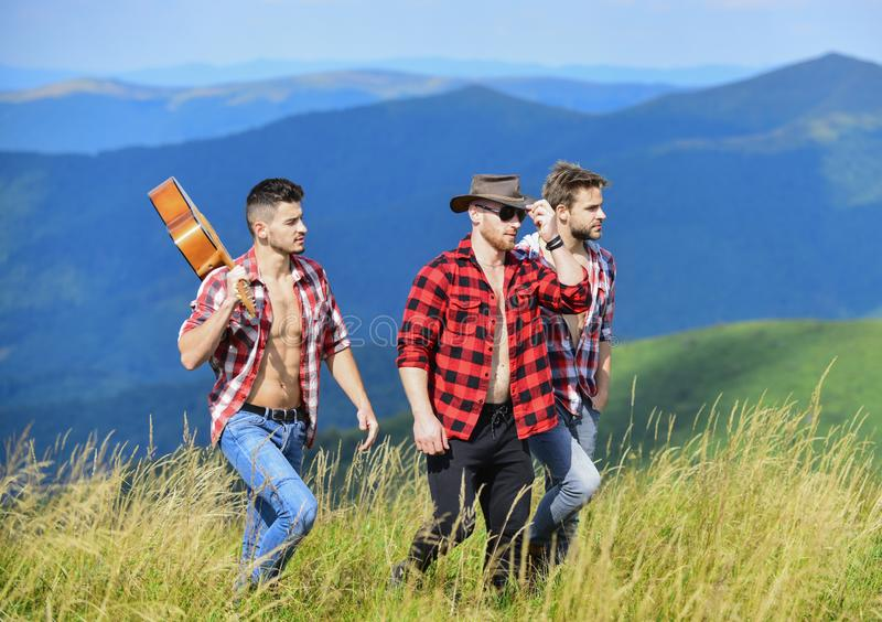 Tourists hiking concept. Group of young people in checkered shirts walking together on top of mountain. Men with guitar. Hiking on sunny day. Hiking with royalty free stock image