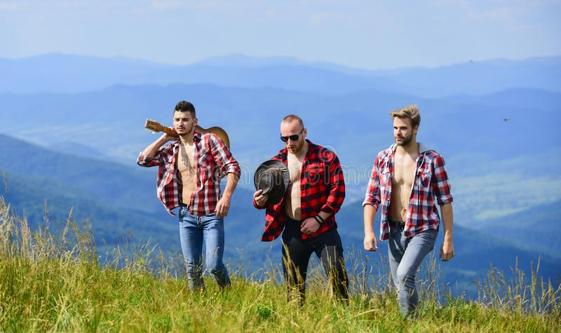 Tourists hiking concept. Hiking with friends. Friendly guys with guitar hiking on sunny day. Enjoying freedom together. Group of young people in checkered royalty free stock photo