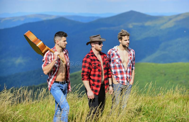 Tourists hiking concept. Hiking with friends. Long route. Adventurers squad. Group of young people in checkered shirts. Walking together on top of mountain. Men royalty free stock images