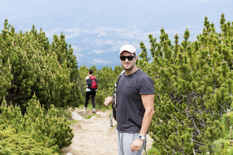 Tourists hiking in a high mountain ,in a pine forest. Hikers with backpack in a high mountain.Beautiful landscape from Bulgaria,Pirin mountain stock image