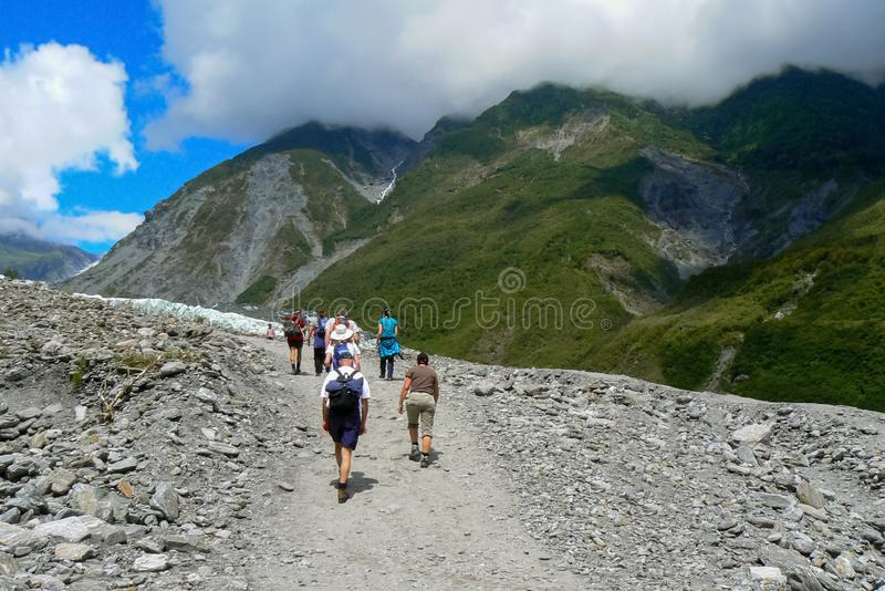 Tourists hiking towards Fox Glacier, South Island, New Zealand. Group of tourists walking up the path to hike Fox Glacier, South Island, New Zealand royalty free stock photography