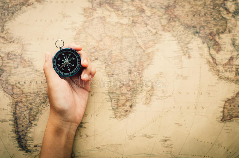 Tourists hold a compass and locate a place on a world map. stock image