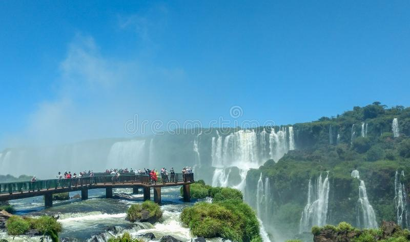 Tourists at Iguazu Falls, one of the world`s great natural wonders, on the border of Brazil and Argentina. Photo taken while travelling around Brazil, Paraguay royalty free stock photography