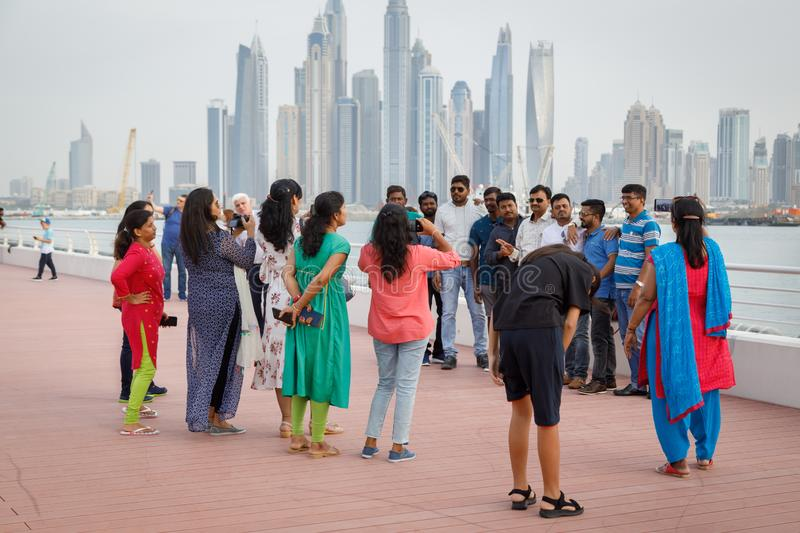 Tourists from India are photographed against the backdrop of beautiful and tall buildings of the city royalty free stock photos