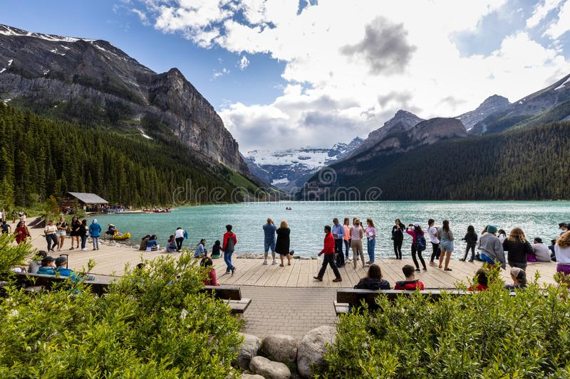 Tourists at Lake Louise in Banff National Park of Canada. The Tourists at Lake Louise in Banff National Park of Canada royalty free stock photography
