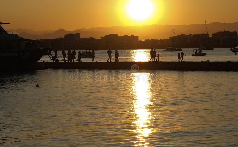 Tourists leave the pleasure boat on the pier in the rays of the golden sunset royalty free stock images