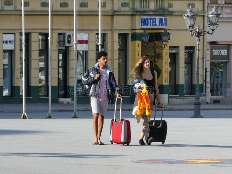 Tourists leaving hotel and walking with suitcases on the street stock photography