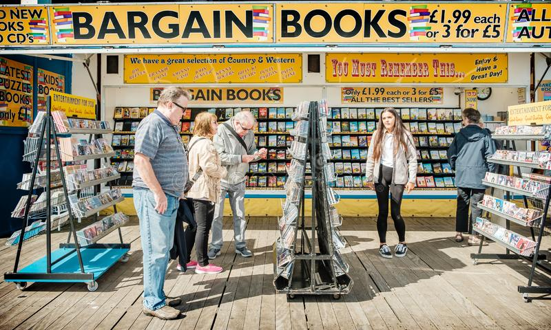 Tourists on Llandudno pier browsing books and CDs at an outdoor bargain book stall stock photos