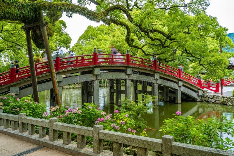 Tourists and local japanese people walk across the beautiful red bridge leading to the famous Tenmangu Shrine in Dazaifu, Japan royalty free stock photo
