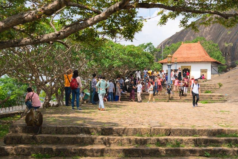 Tourists and local people crowd near entrance to Dambulla Golden. DAMBULLA, SRI LANKA - NOV 2016: Tourists and local people crowd near entrance to Golden cave stock photo
