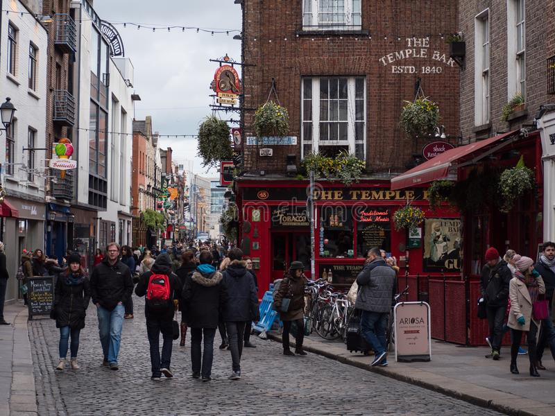People in street, Irish pubs in Temple Bar, Dublin, Ireland. Tourists and local people walk past Irish pubs with colourful floral displays in Temple Bar, Dublin stock photo