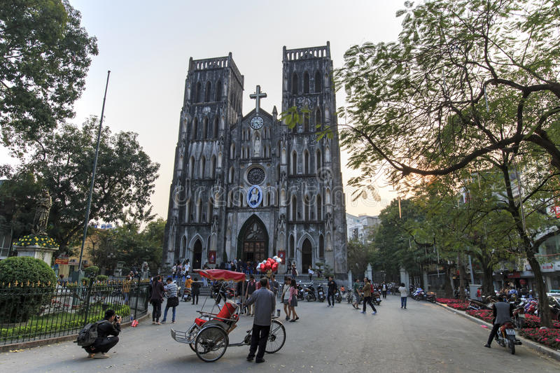 Tourists and local people walking in fron of Saint Joseph Cathedral, the most important church of Hanoi. Hanoi, Vietnam: February 21, 2016: Tourists and local stock photo