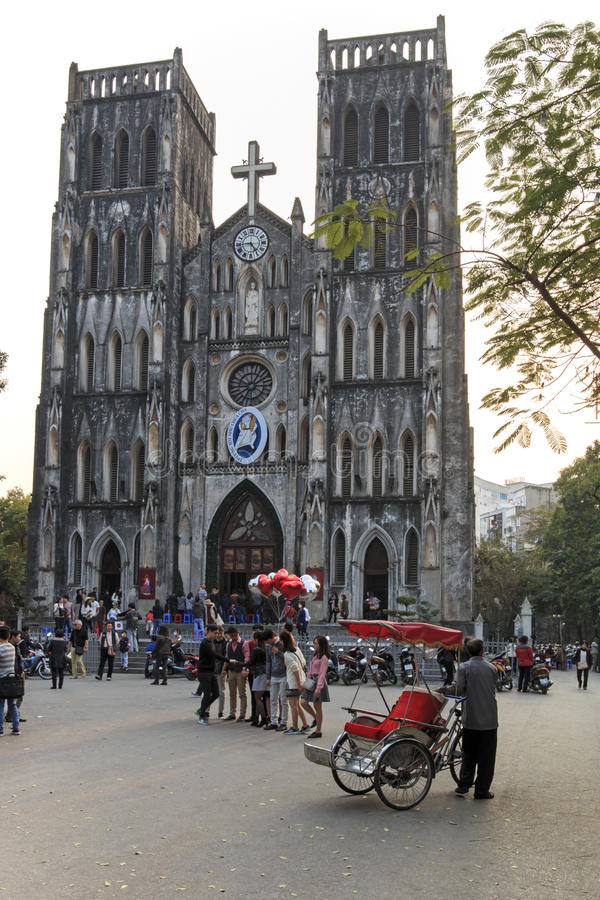 Tourists and local people walking in fron of Saint Joseph Cathedral, the most important church of Hanoi. Hanoi, Vietnam: February 21, 2016: Tourists and local royalty free stock photo