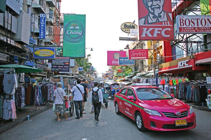 Thailand, Bangkok - August 2019: People and a taxi pass through the iconic Khao San Road in central Bangkok royalty free stock images