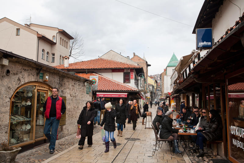Tourists and locals sit in outdoor cafe and walk on Bascarsija area in Sarajevo stock photo