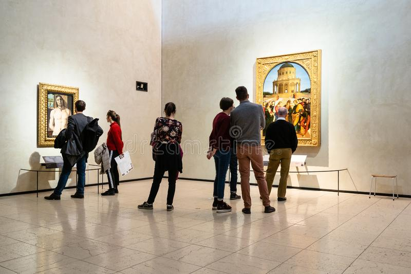 Tourists look paintings in Pinacoteca di Brera. MILAN, ITALY - FEBRUARY 24, 2019: tourists look paintings in Pinacoteca di Brera Brera Art Gallery in Milan. The royalty free stock photography