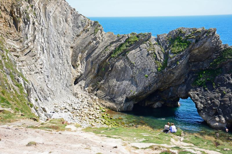 Tourists looking through archway, Lulworth Cove. stock photos