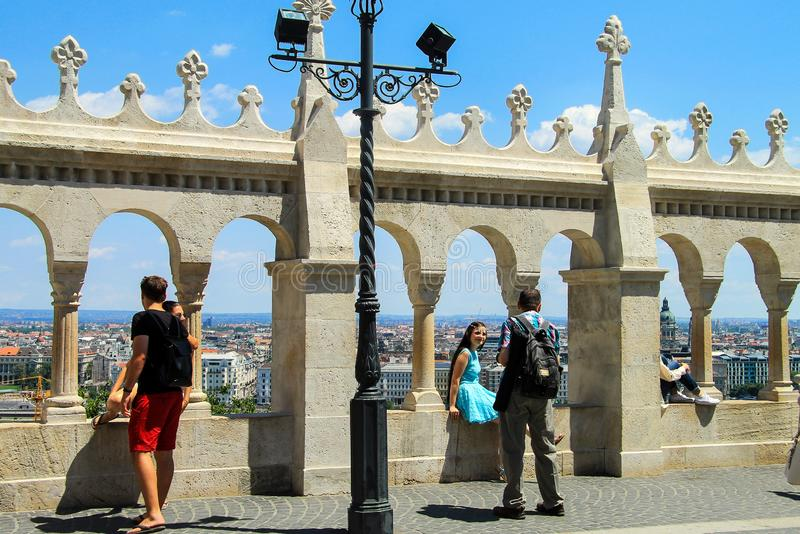 Tourists looking Parliament view through Fishermans Bastion and take pictures on the Buda Hill near old stone fence royalty free stock photo