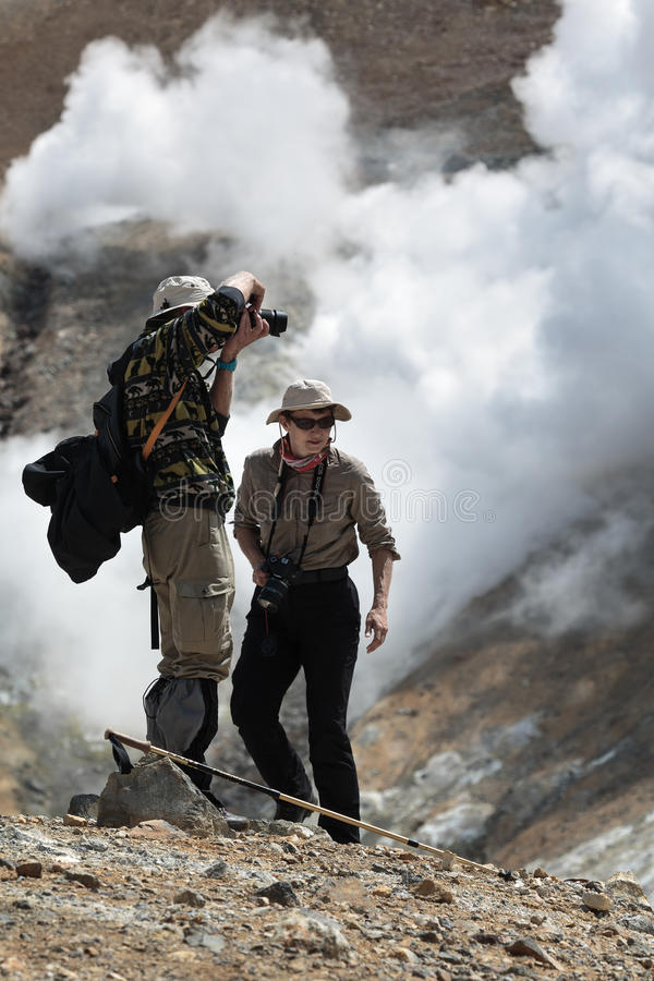 Tourists (man and woman) on crater active volcano. MUTNOVSKY VOLCANO, KAMCHATKA PENINSULA, RUSSIA - JULY 4, 2014: Hiking in Kamchatka - tourists (man and woman) stock image