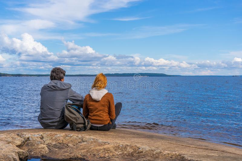 Tourists man and woman sitting on northern lake shore in summer day. People relaxing and admiring beautiful landscape. Travelling stock photos