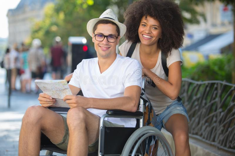 Tourists with map man in wheelchair royalty free stock photos