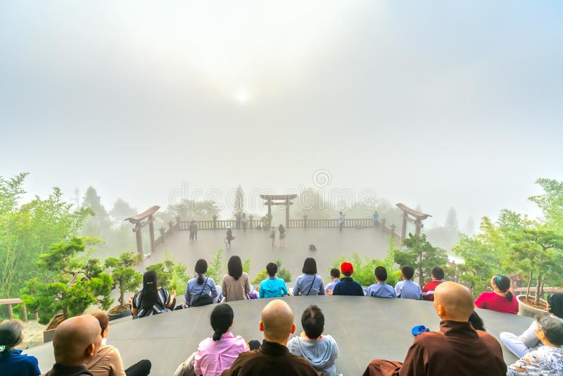 Tourists meditating in front temple as a way to relax soul stock image