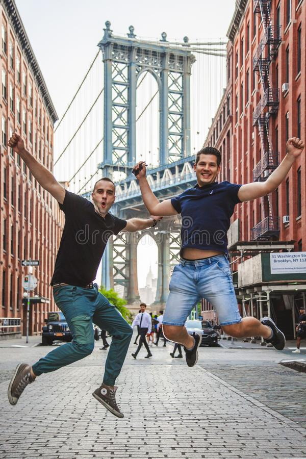 Tourists models enjoying New York City and Dumbo, Brooklyn. Tourists handsome models feeling happy and Manhattan Bridge between Manhattan and Brooklyn over East stock image